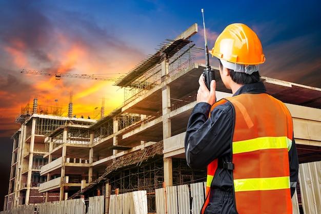 Comando dell'ingegnere edile che parla dalla radio portatile in cantiere