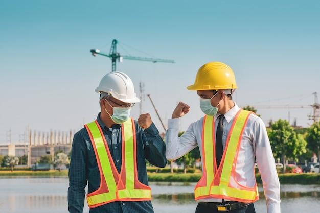 Ingegnere edile stringe la mano senza toccare il sito in costruzione