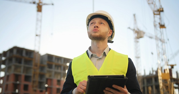 Ingegnere di costruzione in casco bianco e maglia verde al cantiere facendo uso della compressa per lavoro. all'aperto.