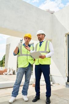 Caposquadra delle costruzioni parlando al lavoratore