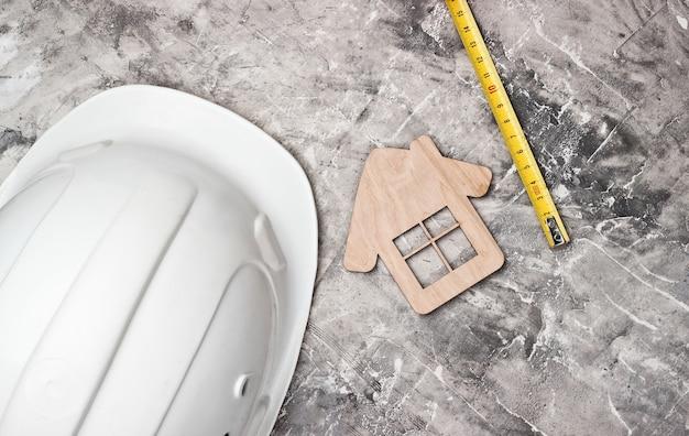 Casco da costruzione, figura di casa, nastro di misurazione su sfondo grigio cemento. vista dall'alto