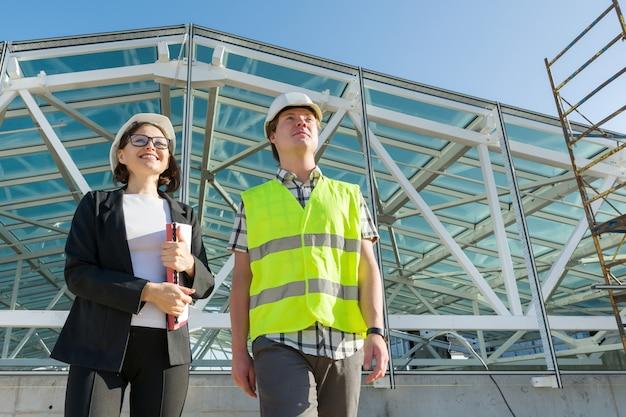 Costruttori di costruzione, uomo e donna in cantiere, team di industriali. costruzione, lavoro di squadra e concetto di persone, copia dello spazio