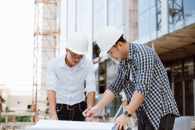 Direttore della costruzione e team di ingegneri che controllano il piano in cantiere. attrezzatura per il transito di teodolite. team di ingegneri. lavorando in cantiere.