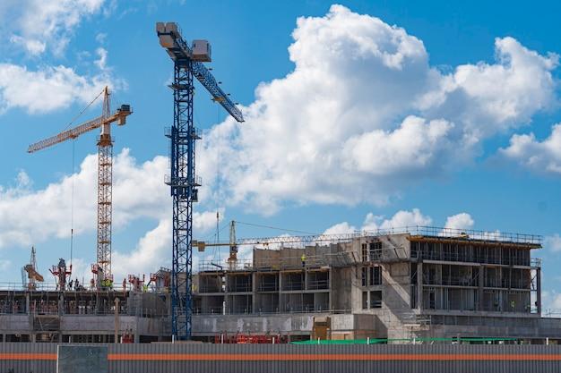Costruzione di un edificio multipiano. gru d'alta quota. sfondo - cielo azzurro con nuvole.