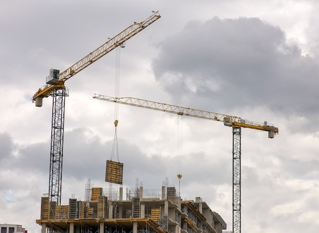 Costruzione di edifici multipiano con gru. i lavoratori lavorano sulla costruzione di oggetti.