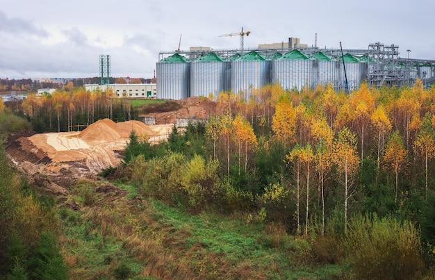 Costruzione serbatoi di stoccaggio del gas naturale e serbatoio dell'olio in impianti industriali. pioggia nuvolosa e foresta autunnale