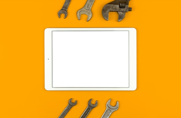 Concetto di mockup di riparazione di costruzione, tablet con schermo bianco vuoto sul tavolo con strumenti e attrezzature di servizio, sfondo giallo, vista dall'alto, disposizione piatta e foto dello spazio della copia