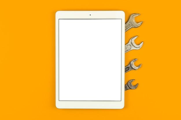 Schermata di mockup del servizio di costruzione, tablet sul tavolo con strumenti professionali, sfondo arancione, vista dall'alto, disposizione piatta e foto dello spazio di copia