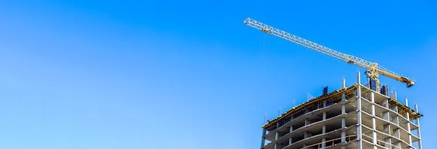 Cantiere e grande gru gialla sullo sfondo del banner panoramico del cielo blu con foto dello spazio della copia