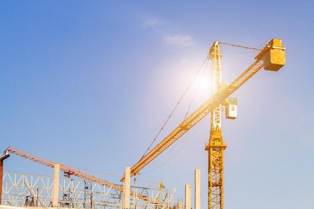 Un cantiere tra cui diverse gru che lavorano su un edificio, boom gru sulla costruzione di un grattacielo e impalcature nell'edificio, con cielo blu
