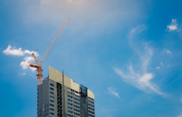Cantiere con gru e costruzione. settore immobiliare. la gru usa la bobina che solleva l'attrezzatura nel cantiere. edificio in acciaio e cemento.