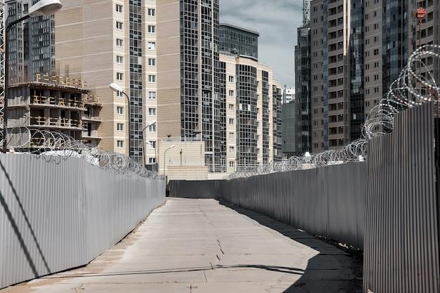 Cantiere con recinzione e strada in cemento sullo sfondo di un complesso di appartamenti residenziali in fase di creazione. vista della zona di pericolo industriale. concetto di ristrutturazione degli alloggi. copia spazio