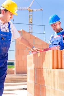 Operaio di cantiere o muratore con elmetti che controlla muri con livella a bolla o edificio o posa o muratura muro su edificio