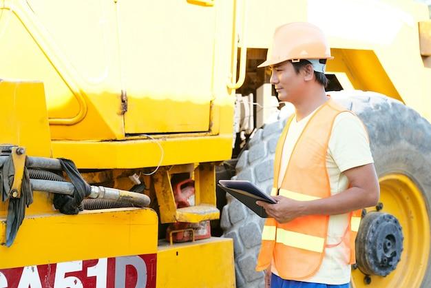 Operaio di cantiere con computer tablet che controllano le macchine prima di iniziare la giornata lavorativa