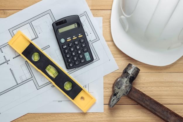 Forniture da costruzione. casco di sicurezza da costruzione bianco con blueprint, livello, calcolatrice su assi di legno. idea di costruzione. vista dall'alto