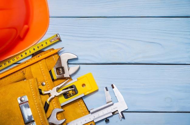 Il kit di strumenti di costruzione per un costruttore in una borsa su assi di legno blu è posto anche per la pubblicità
