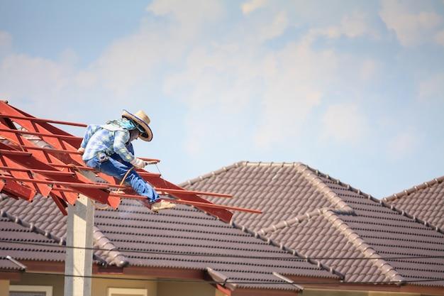 Saldatori edili che installano la struttura del telaio in acciaio del tetto della casa in un cantiere edile con nuvole e cielo