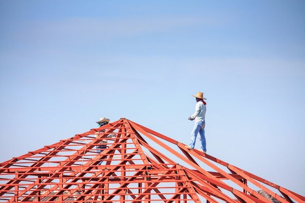 Lavoratori del saldatore edile che installano la struttura del telaio in acciaio del tetto della casa in cantiere con nuvole e cielo