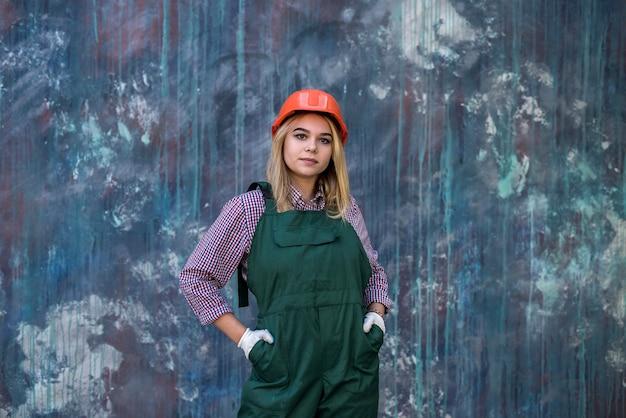 La donna della costruzione in uniforme rossa e casco, guanto protettivo posa per la macchina fotografica e si prepara a riparare l'appartamento. occupazione di lavoro di costruzione.