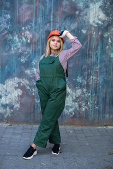 Donna di costruzione in uniforme rossa e casco, guanto protettivo posa per la fotocamera e si prepara a riparare l'appartamento