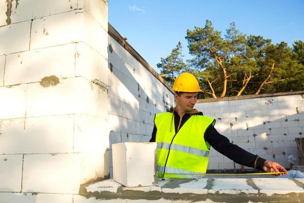 L'operaio edile al cantiere misura la lunghezza della finestra