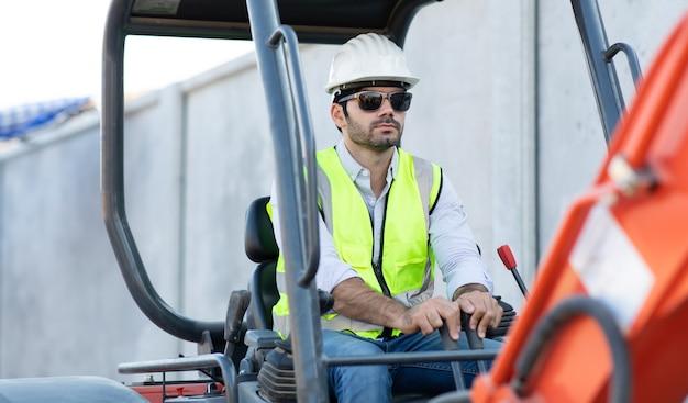 Operaio edile che guida l'escavatore o il retroescavatore in cantiere. giovane uomo ispanico che opera attrezzature pesanti