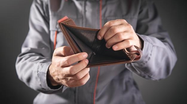Operaio edile che tiene portafoglio vuoto.