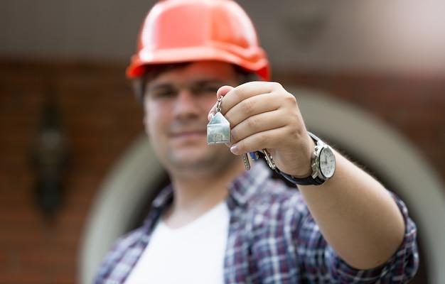 Operaio edile che tiene in mano le chiavi della nuova casa