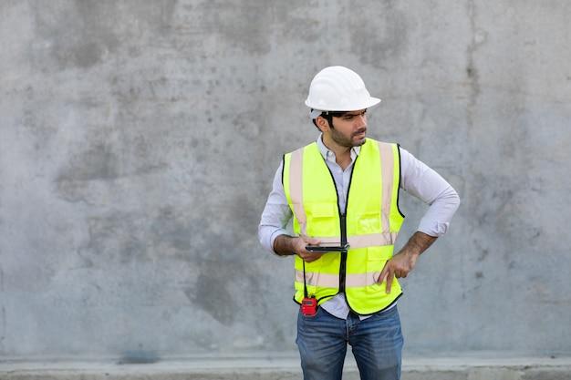 Operaio edile tenendo e guardando sulla tavoletta digitale isolare su sfondo grigio cemento. ingegnere di progetto in cantiere.