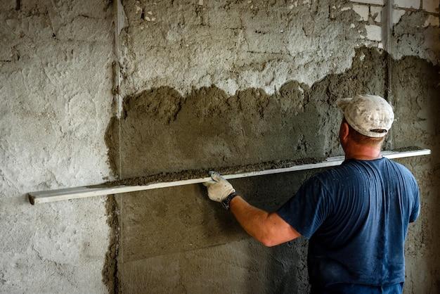 Operaio edile intonaco muro con livellatore.