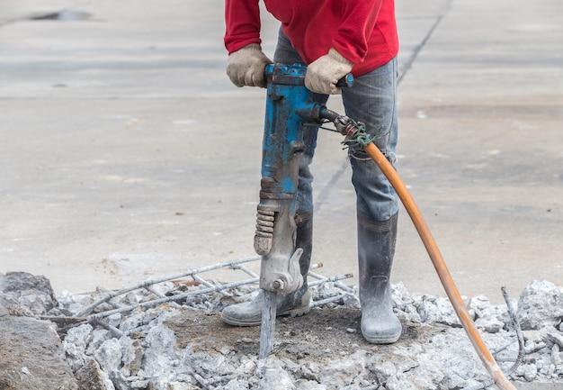 Il muratore rimuove il calcestruzzo in eccesso con la perforatrice nel cantiere