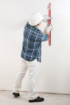 L'operaio edile in un casco di sicurezza controlla un muro bianco liscio con un livello di costruzione