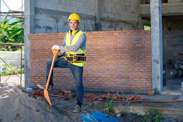 L'operaio edile in uniforme e attrezzatura di sicurezza ha un lavoro in cantiere
