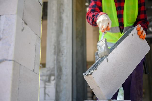 Operaio edile stiamo intonacando la malta adesiva che utilizza calcestruzzo leggero per la costruzione. tecniche per l'applicazione di malta adesiva in un cantiere edile.