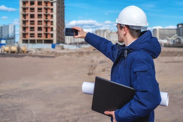 Un operaio edile in un casco bianco con un laptop e documenti sotto il braccio