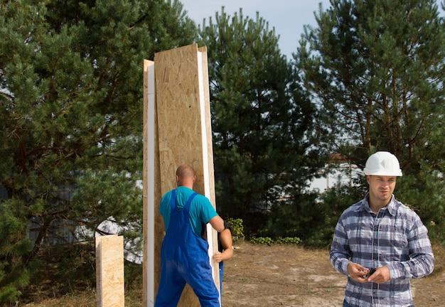 Operai edili impegnati a erigere un pannello a parete in legno isolato ad angolo e un ingegnere sul posto che lavora su una nuova costruzione di casa