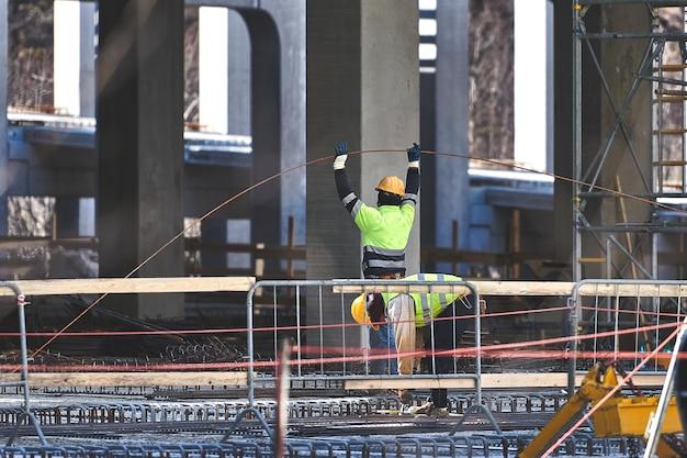 I lavoratori edili in cantiere lavorano con rinforzi in calcestruzzo
