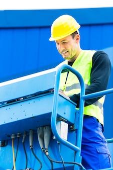 Operai edili o gruista sul posto che guida la rampa di sollevamento idraulica con banco di controllo