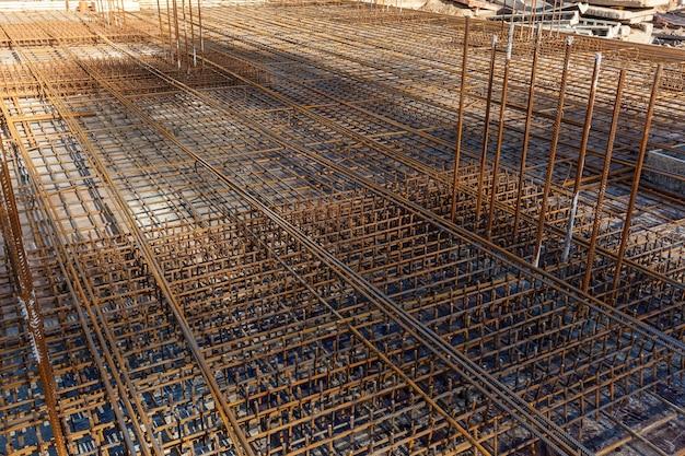 Lavoratori edili che fabbricano barra di rinforzo in acciaio nel cantiere. la barra di rinforzo era legata insieme usando un filo minuscolo.