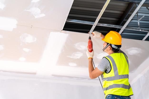I lavoratori edili che utilizzano un trapano elettrico installano la casa del soffitto nell'edificio in costruzione, idee per l'installazione del soffitto