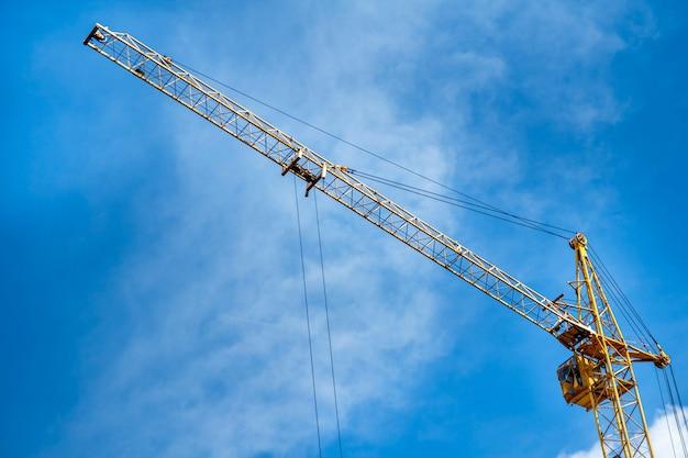 Gru gialla della costruzione contro lo sfondo di un cielo blu.