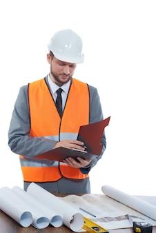Costruttore che indossa giubbotto ed elmetto protettivo di sicurezza che fa le note sui suoi appunti isolati su bianco.