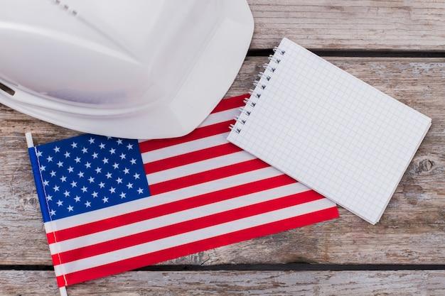 Casco costruttore costruttore con noi bandiera e blocco note vuoto. posto per lo spazio della copia. concetto di lavoratori americani.