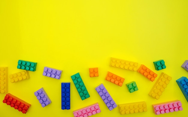 I dettagli del costruttore sono sparsi su uno sfondo giallo. blocchi di costruzione multicolori.