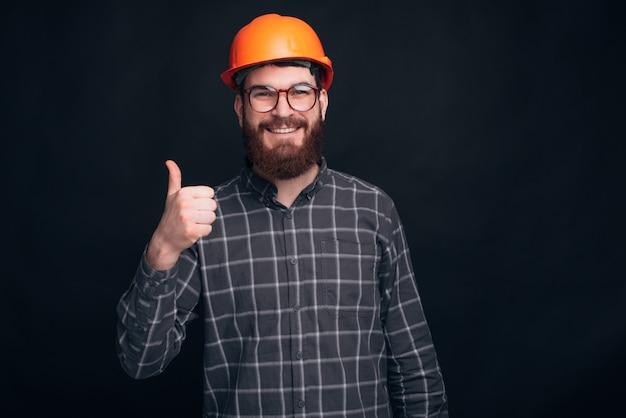 Un costruttore sta mostrando un pollice e sorridendo alla telecamera vicino a un muro nero.