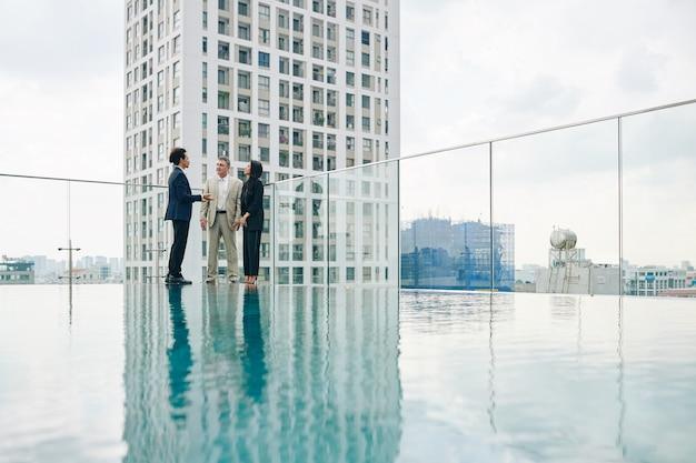 Responsabile della società di costruzioni che mostra un nuovo edificio agli investitori quando sono in piedi sul tetto vicino alla piscina