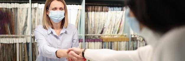 Il consulente e il cliente si stringono la mano nel concetto di transazione di successo del negozio di tessuti