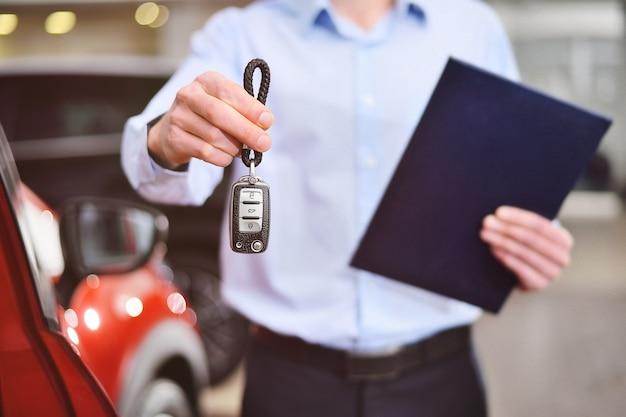 Un consulente o manager di una concessionaria di automobili e di uno showroom di automobili tiene in mano le chiavi della macchina e un tablet