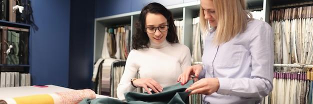 Il consulente con il cliente sta scegliendo i tessuti nella vendita del negozio del concetto di tessuti