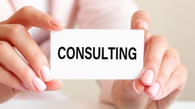 La consulenza è scritta su un biglietto da visita bianco nelle mani di una donna. sfondo rosa. concetto di business e pubblicità